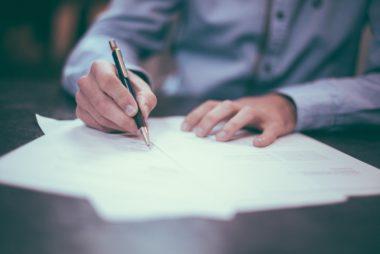 man writing an application form